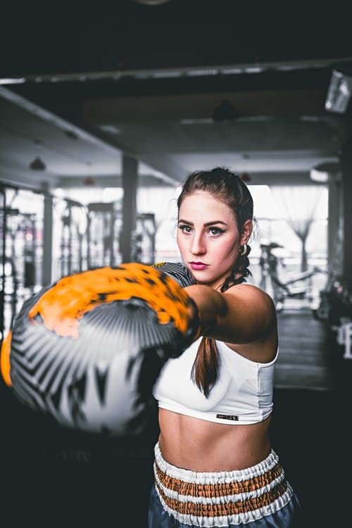 Young determined woman in modern boxing gloves