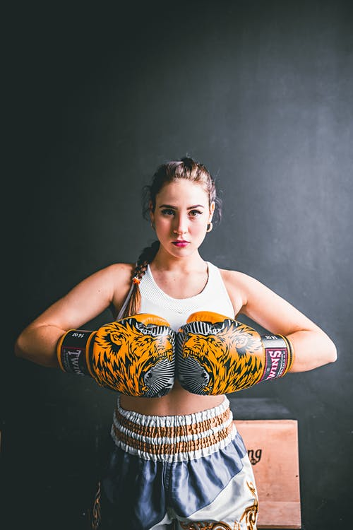 Confident young woman in boxing gloves