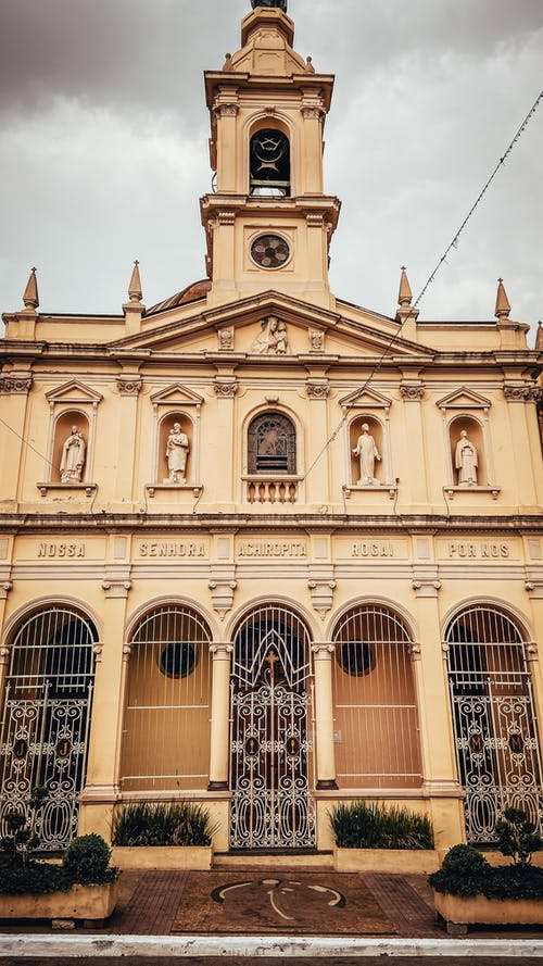 Low angle exterior of aged Paraquia Nossa Senhora Achiropita church with bell tower and arched windows located in Sao Paulo