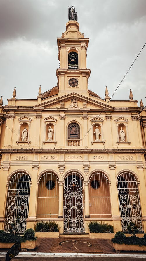 Low angle exterior of aged Paroquia Nossa Senhora Achiropita church with statues and bell tower against overcast sky in Sao Paulo