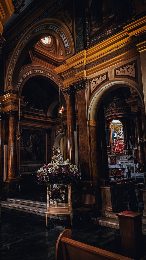 Interior details of aged Paroquia Nossa Senhora Achiropita church with wooden arched ornamental walls and pictures