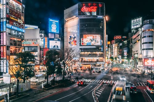 Spectacular scenery of various modern commercial buildings with colorful illumination located in Shibuya district of Tokyo at night