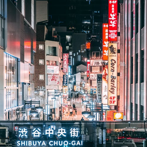 Glowing signboards on contemporary buildings in city downtown at night