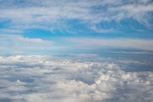 Breathtaking aerial view of of thick white cumulus and cirrus clouds floating in blue sky on sunny day