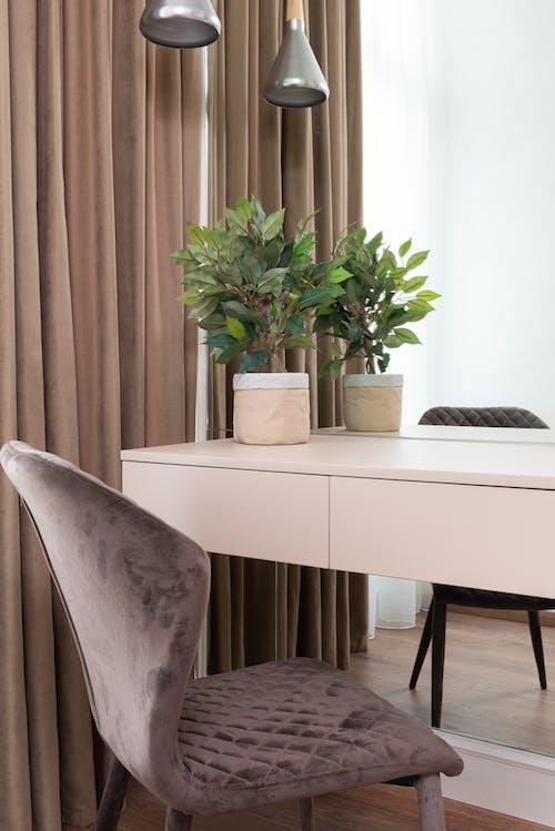Comfortable chair near table against big mirror