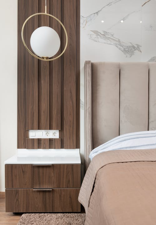 Interior of modern hotel room with bed next to bedside table under lamp hanging from ceiling