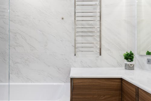Interior of light modern bathroom with potted green plant on cabinet under mirror on white tile