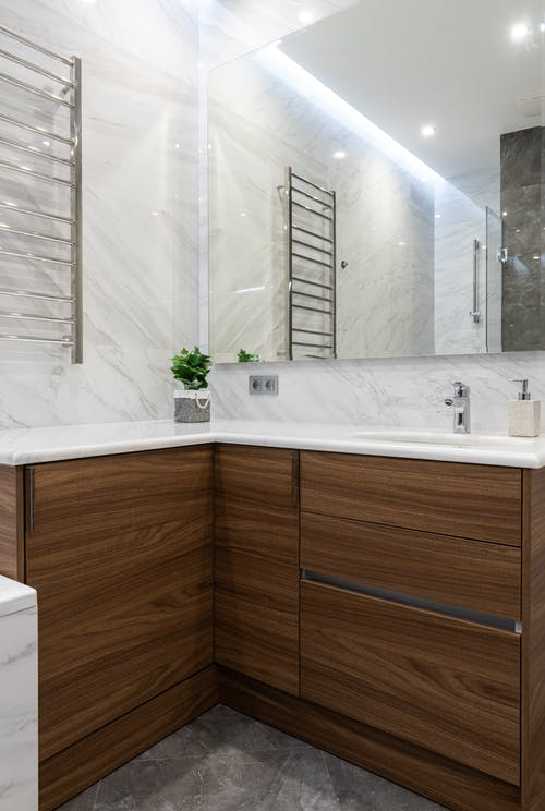 Interior of modern light bathroom with sink and tap on cabinets under mirror
