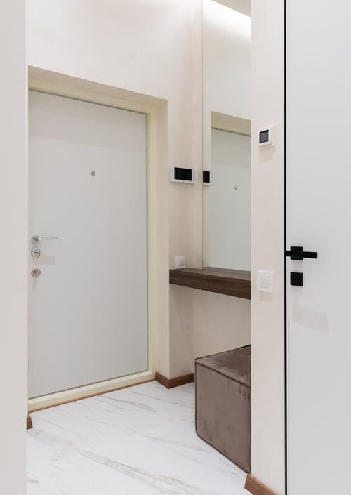 Interior of contemporary apartment with beige walls white doors and comfortable pouf placed near big mirror in light hall