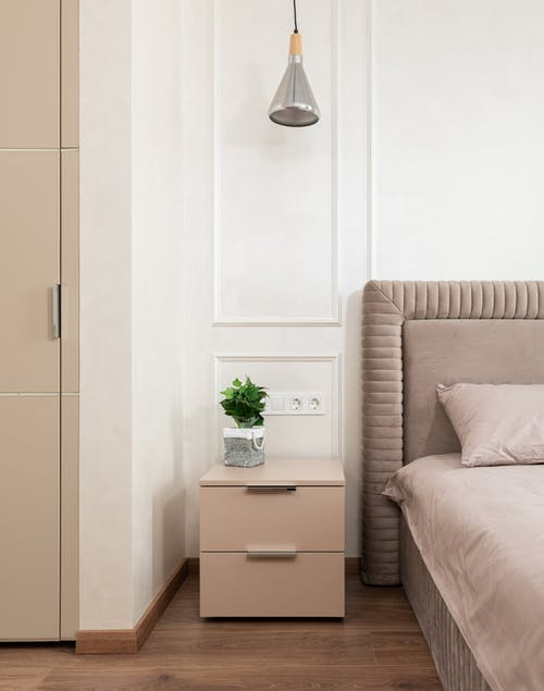Bedside table with potted plant placed near comfortable bed with pink coverlet and pillows in cozy room at home
