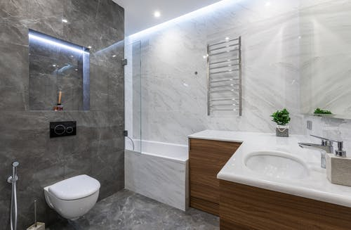 Interior of contemporary bathroom with white washbasin bathtub and toilet with bidet in modern apartment