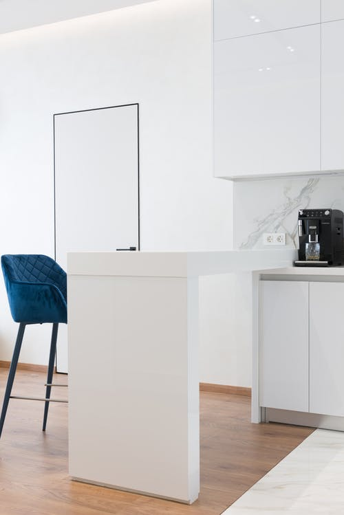 Comfortable blue chair placed near counter in contemporary kitchen with minimalist while furniture and modern appliances