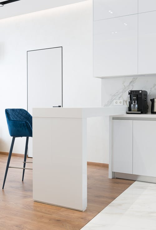 White counter with blue bar chair in spacious kitchen with minimalist furniture and modern appliances in daylight