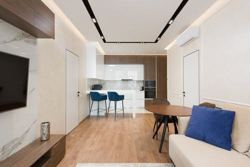 Interior of modern apartment with living room with comfy sofa and wooden furniture near kitchen zone with counter and white cabinets