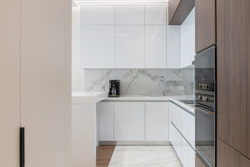 Minimalist interior of small kitchen with white and wooden cupboards and modern appliances in light apartment