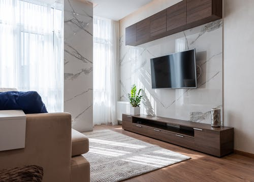 Modern TV set hanging on wall between wooden cabinets in front of comfortable sofa in light living room