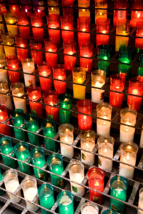 Lighted Candles In Colored Glass Bottles