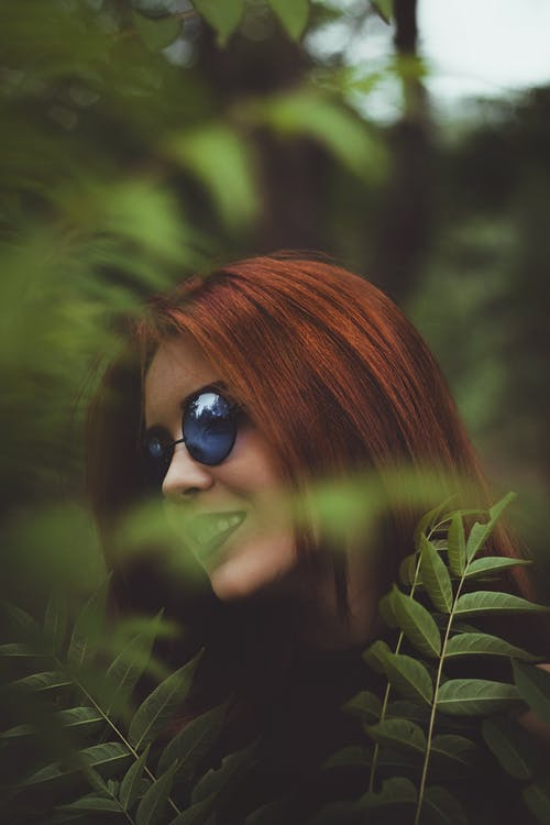 Side view of self assured young female with ling red hair in trendy sunglasses smiling while resting in lush green garden