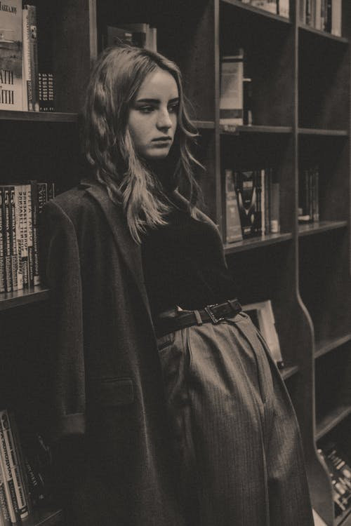 Black and white of thoughtful young female in trendy outfit leaning on bookshelf in library and looking away