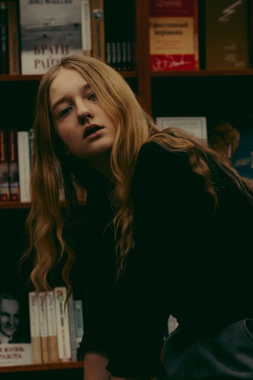 Stylish young woman spending time in library and looking at camera