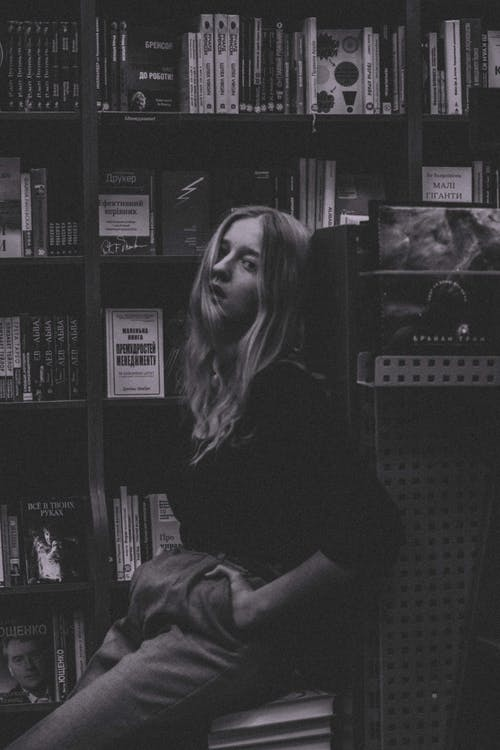 Side view of black and white ponder stylish female student with long wavy hair sitting near bookshelf in library and looking at camera
