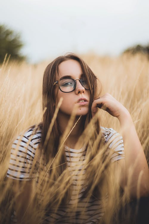 Relaxed young woman sitting in dry grassy meadow on cloudy day