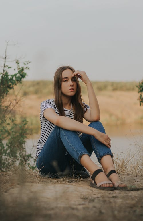 Full body of thoughtful young female millennial in casual outfit touching forehead while sitting on rural ground near meadow during holiday in countryside and looking at camera