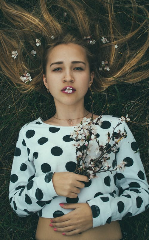 Top view of peaceful young female with long blond hair in stylish clothes lying on grassy meadow with bunch of fresh delicate wildflowers in hand and petals on lips