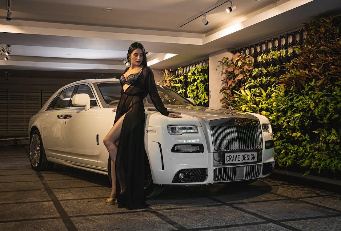 Woman in Black Long Sleeve Dress Standing Beside White Car