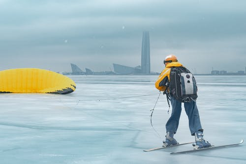 Man in Black Jacket and Blue Denim Jeans Holding Yellow Surfboard on Snow Covered Ground during