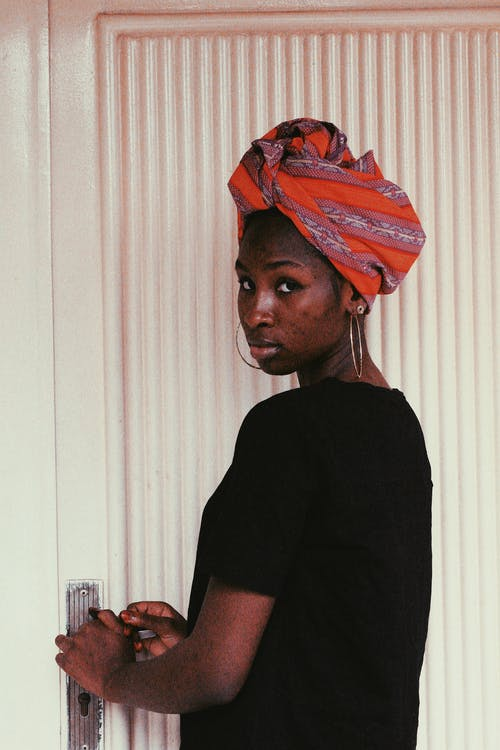 Side view of calm black female in black t shirt with headscarf looking at camera while opening door