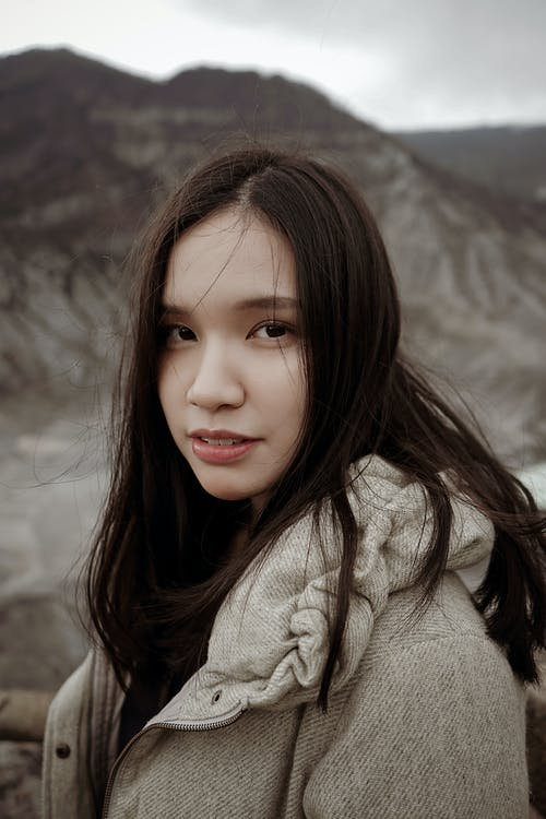 Charming female with dark hair wearing warm jacket standing near fence at viewpoint against high rocky mountain