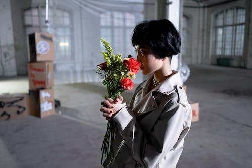 Woman In Beige Coat Holding Bouquet Of Flowers