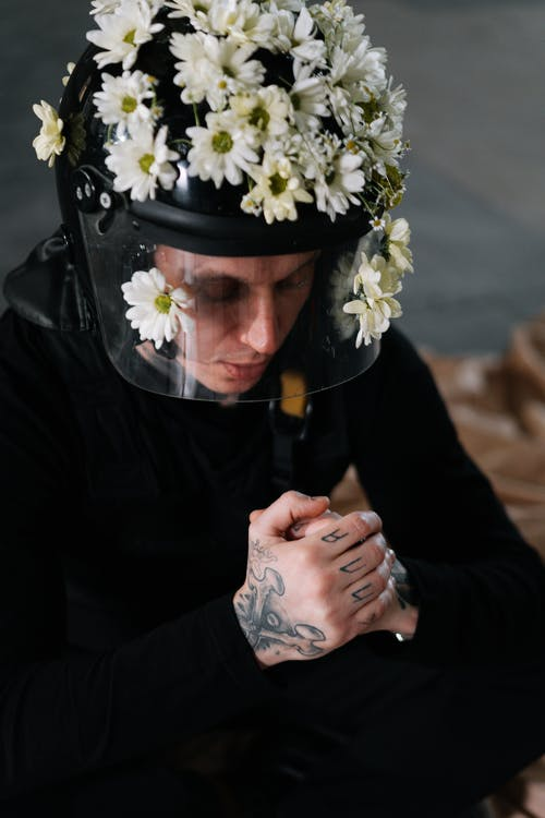 Man Wearing A Helmet Covered With Flowers