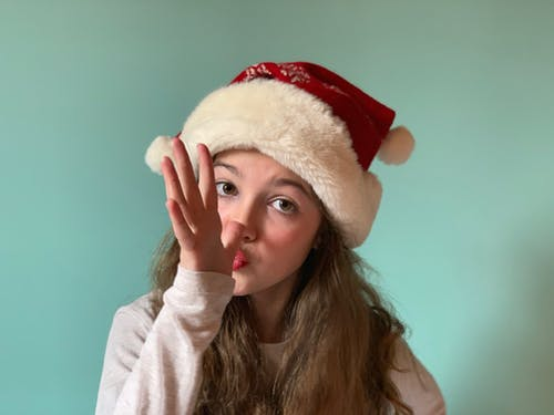 Young Woman With Santa Hat Doing A Hand Gesture