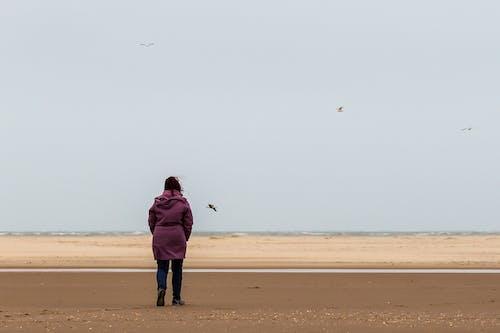 Woman Walking Alone On Seaside Looking At The Horizon