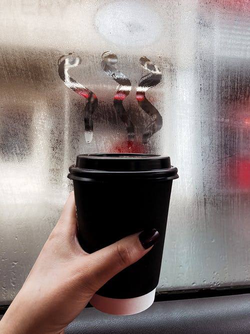 Hand woman holding cup of takeaway coffee near misted window