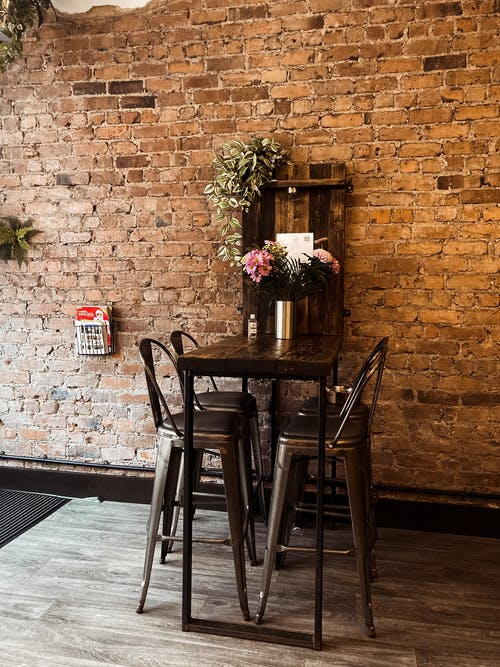 Flowers vase arranged on wooden table with tall chair placed near aged brick wall in classic styled cafe