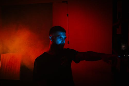 Concentrated male with eyes lightened by multimedia projector standing in dark room with red illumination