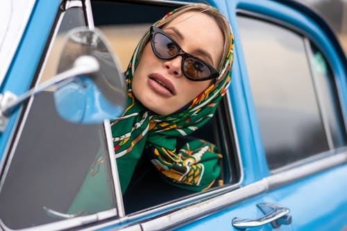 Stylish woman driving car and looking at window
