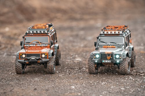 Small toy figures of off road cars with shining headlights placed on ground