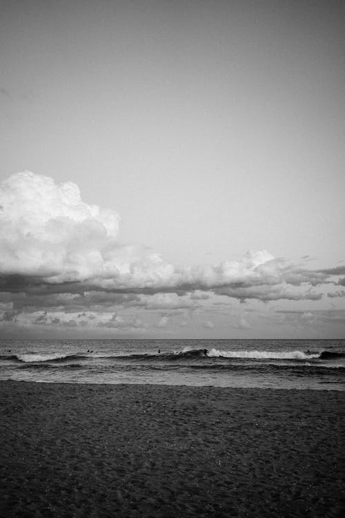 Black and white of empty sandy beach near waving rippling foamy sea with surfers under cloudy sky