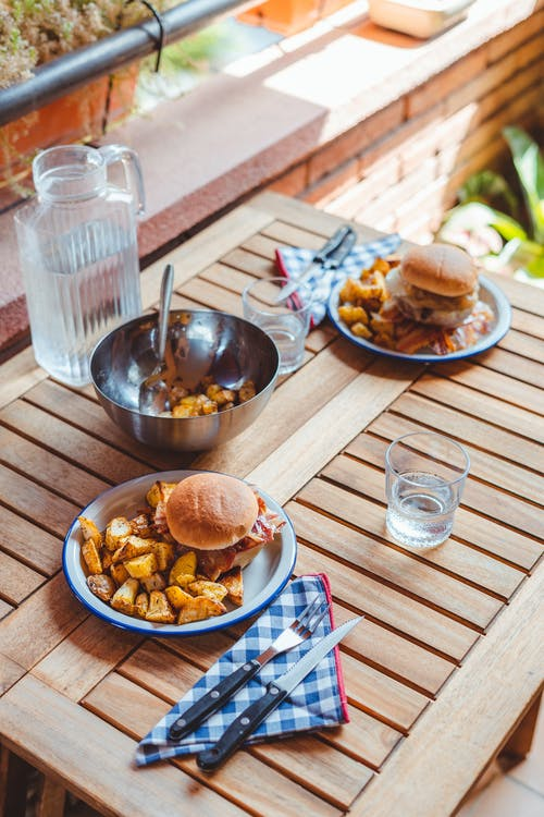 From above of tasty homemade burgers on plate with roasted potato served on table with jug of water and tableware