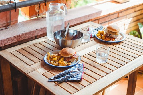 Appetizing burgers and potato wedges on table
