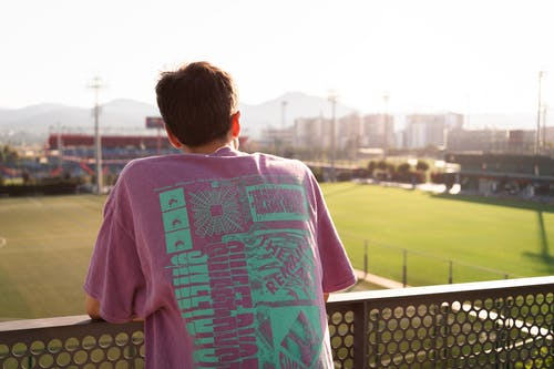 Back view of anonymous young male in colorful t shirt standing leaning on metal fence on stadium and looking at play filed