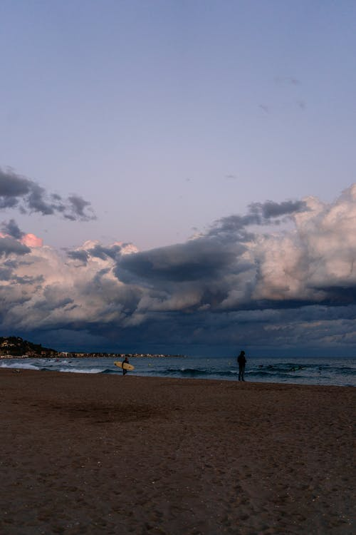 Sandy beach with surfers in evening