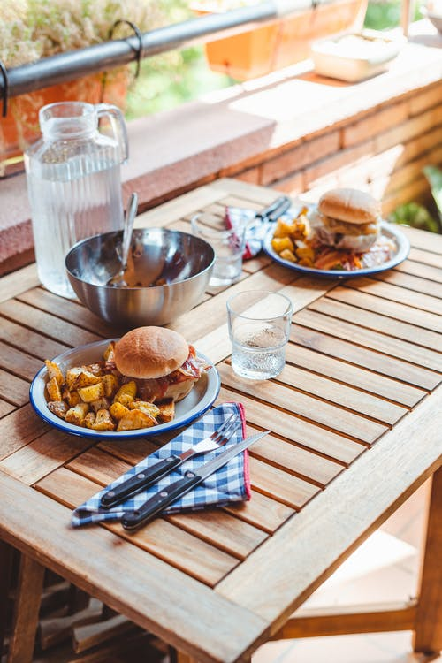 High angle of wooden table served with tasty homemade burgers on plates with roasted potato and jug of water