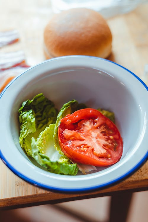 Plate with salad of tomato and lettuce leaves
