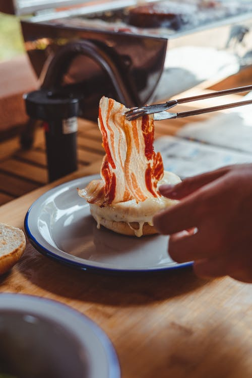 Crop anonymous person taking slice of delicious bacon from plate with yummy bread while having dinner