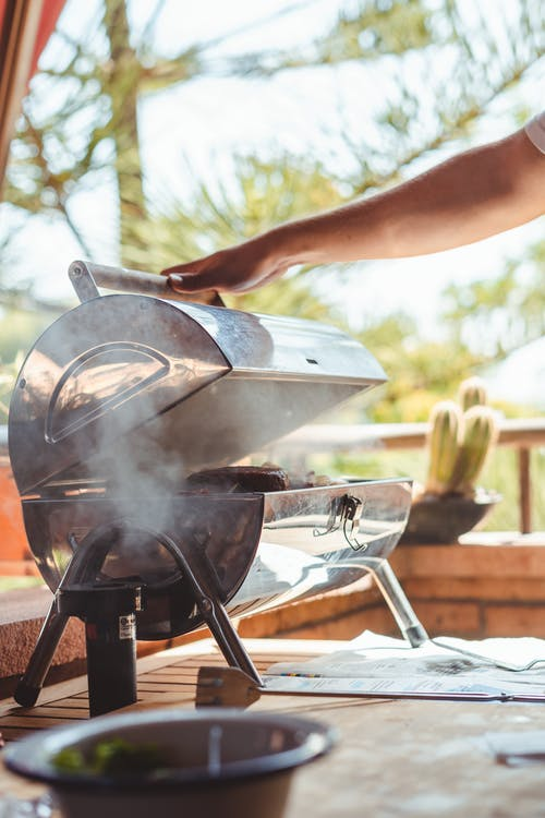 Crop person cooking meat on grill